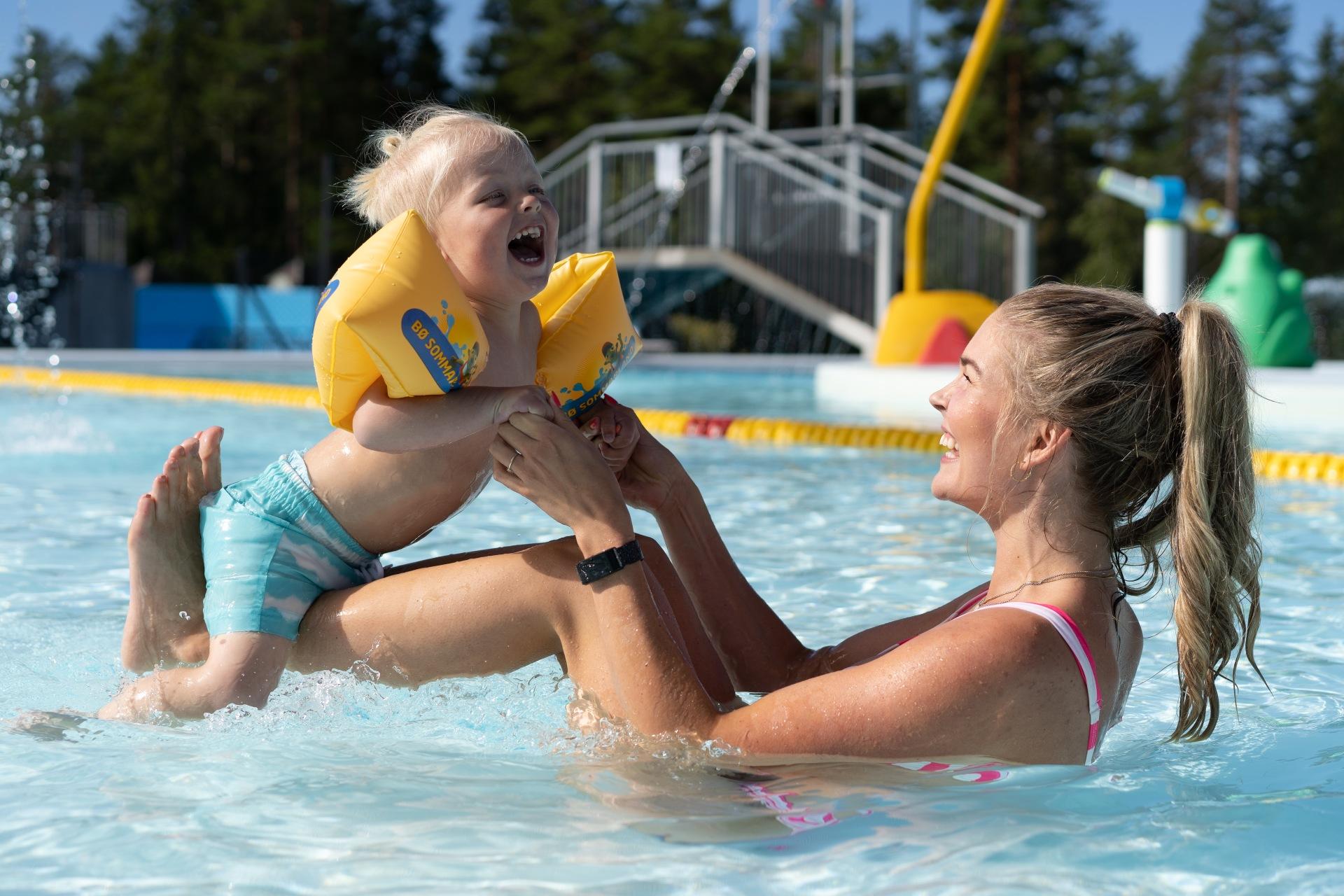 Mor og sønn leker i bassenget