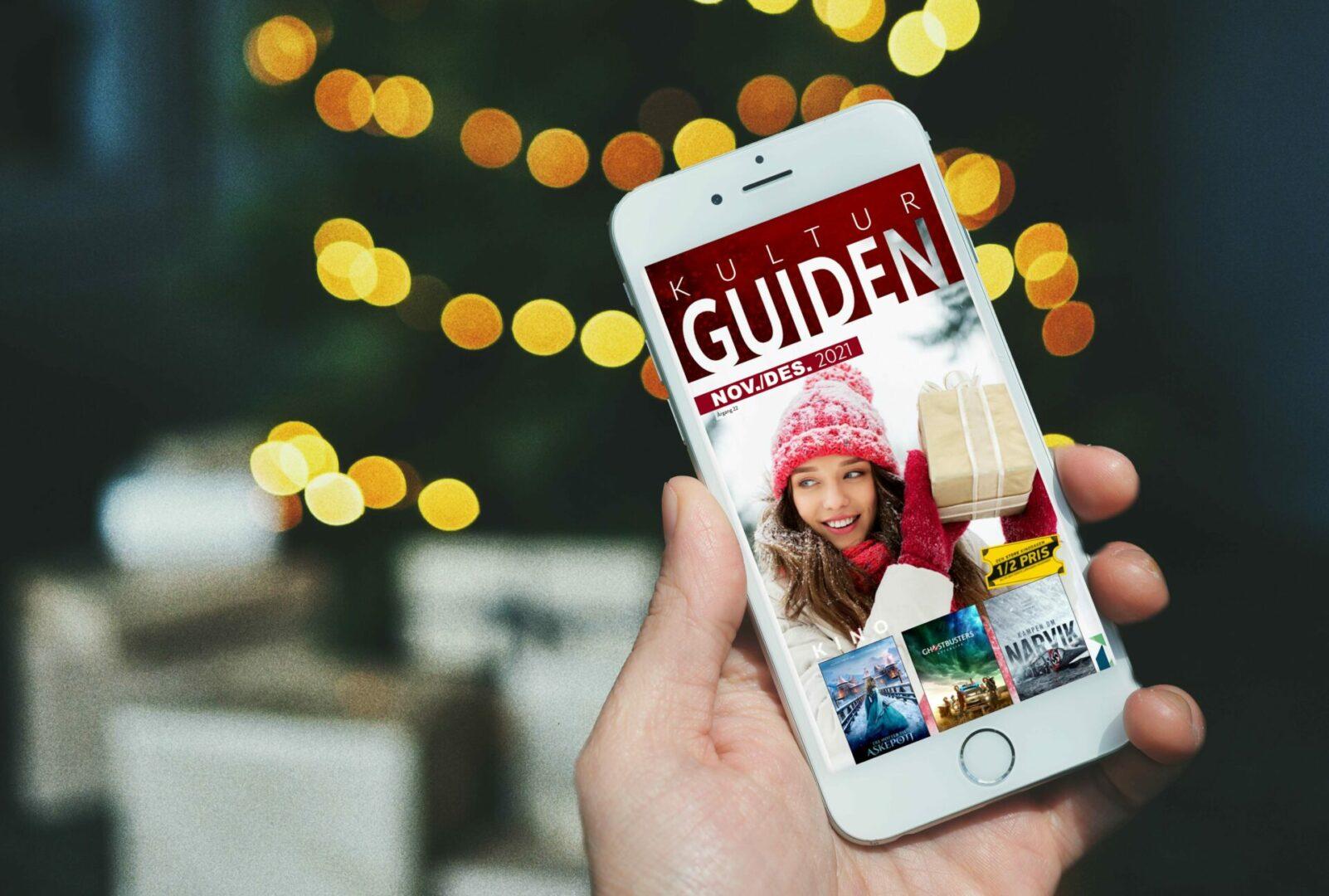 Kulturguiden på mobilen foran juletreet