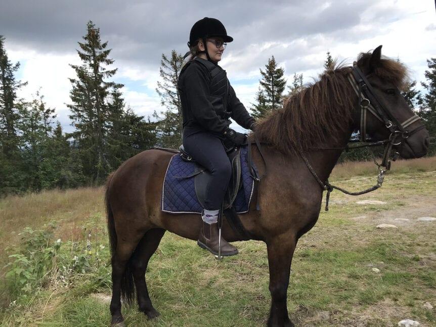 Jente som sitter på hest i spesial laget sete